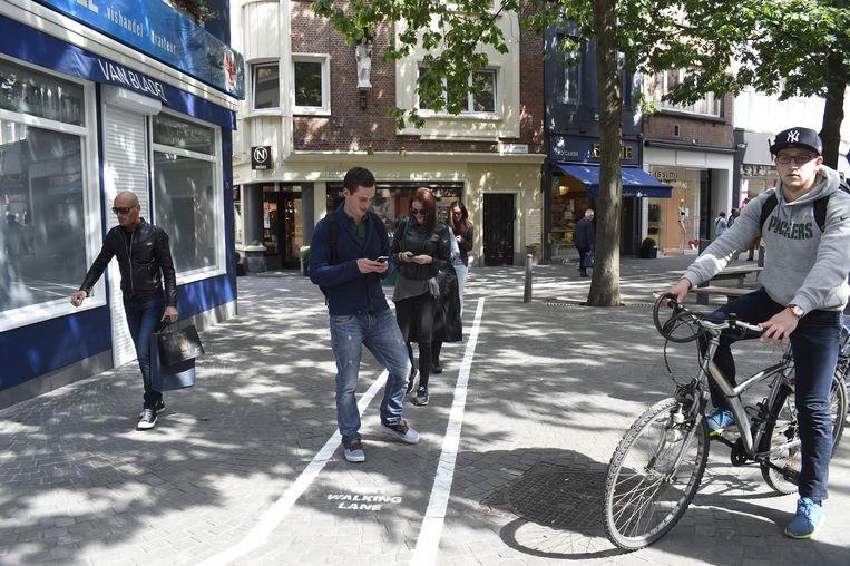 Enkele smartphonegebruikers maken in de Korte Gasthuisstraat toch even gebruik van de 'Text Walking Lanes'.