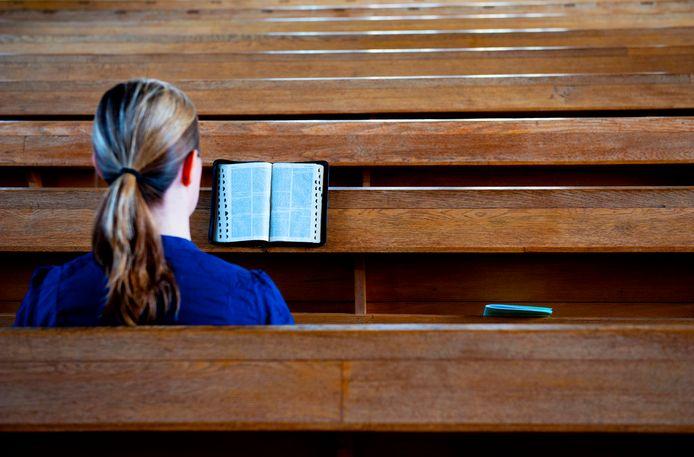 Kerkganger leest in de Bijbel.  Foto ter illustratie.