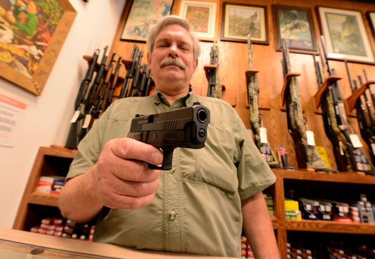 Wapenverkoper Bob Croy met een Sig Sauer 9mm handwapen (Archiefbeeld). Beeld EPA