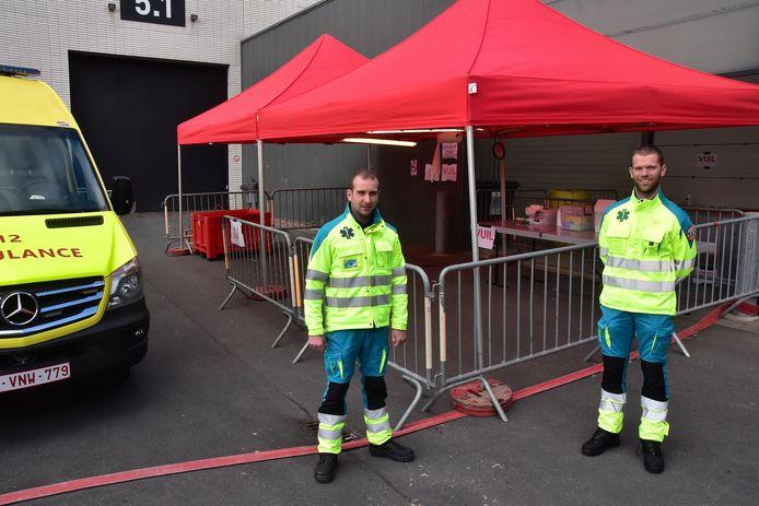 Ambulanciers Jonas Lapauw (links) en Pieter-Jan Vancraeynest, bij de ingang van de ontsmettingszone op de terreinen van Kortrijk Xpo.