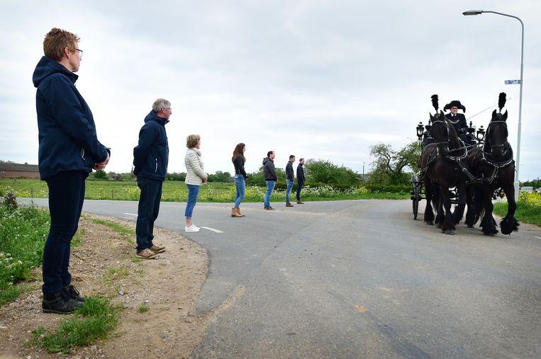 Langs de route waar een uitvaartstoet langskomt staan mensen anderhalve meter uit elkaar, afgelopen april, in Horssen. Beeld Marcel van den Bergh