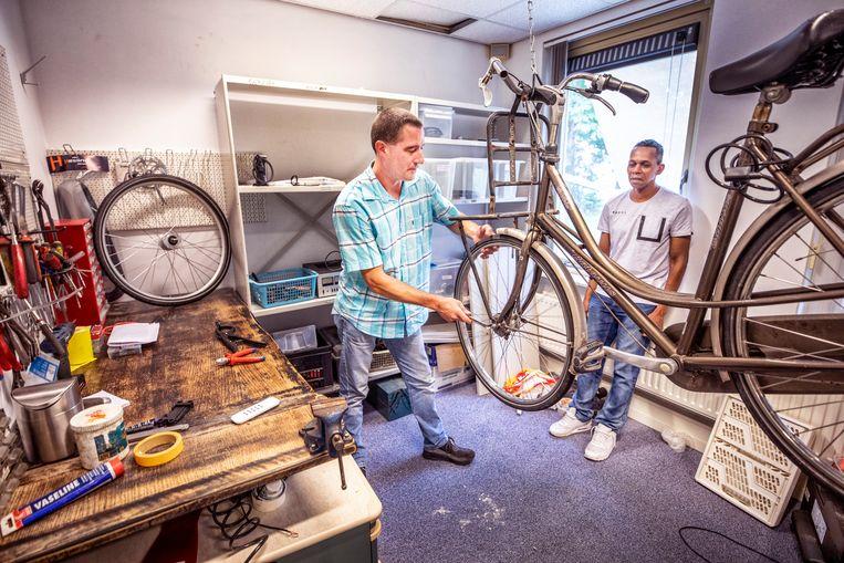 Bij coöperatie Het Lichtpunt in Alkmaar worden bijstandsgerechtigden omgeschoold tot ondernemers. Hier leert Ramses Kolenbrander het vak van fietsenmaker. Rechts staat Timothy Stewart die wil beginnen als kok.  Beeld Raymond Rutting/de Volkskrant