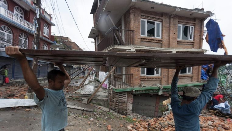Inwoners van Kathmandu dragen puin na de tweede krachtige aardbeving afgelopen dinsdag in Nepal. Beeld epa