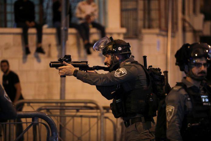 Een Israëlische agent richt om te schieten tijdens ongeregeldheden met Palestijnse demonstranten.