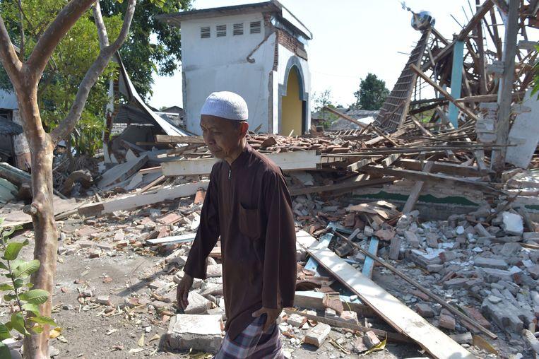 Een inwoner van Lombok loopt een moskee voorbij die het begaf tijdens de  aardbeving van 12 augustus. Al sinds 29 juli wordt het eiland zwaar getroffen.