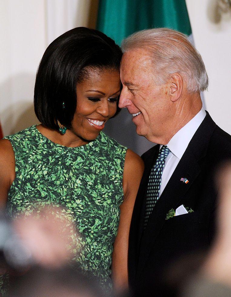Biden omhelst, kust, aait, snuffelt, pakt mensen bij de nek en bij de schouders, raakt met zijn voorhoofd een ander voorhoofd. Hier met voormalig first lady Michelle Obama. Beeld EPA