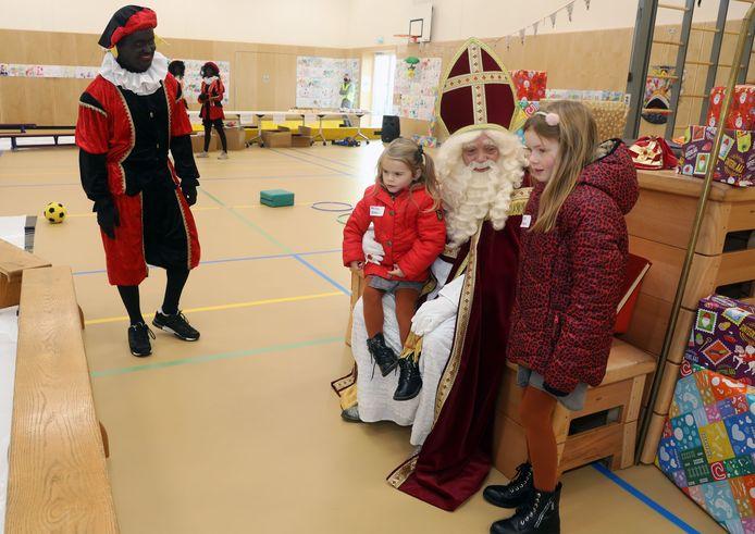Milou en Elise mogen héél even bij Sinterklaas voor de foto.