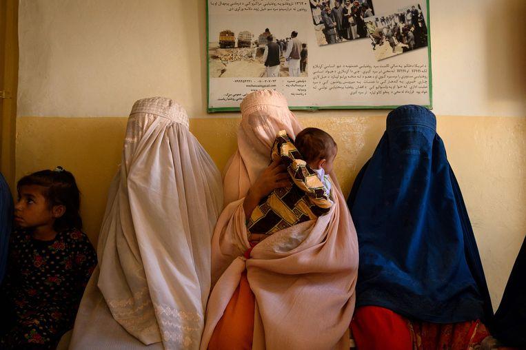 Op deze foto, gemaakt op 1 oktober 2020, wachten vrouwen met hun kinderen in een door de overheid gerunde kraamkliniek in het district Dand in de provincie Kandahar. Sinds de terugtrekking van buitenlandse troepen in Afghanistan begon en een daaropvolgende escalatie van het geweld van de Taliban, zijn er tekenen geweest dat de reeds beperkte kraamzorg nog verder zou kunnen worden beperkt, aangezien duizenden vrouwen ontheemd zijn en wegen steeds gevaarlijker. Beeld AFP