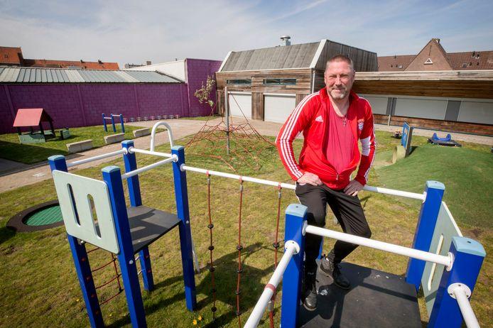 SSKB-voorzitter Willem Hoogkamer in de speeltuin in de Abeelstraat in Breda. Achter hem het gebouw dat wordt gesloopt.