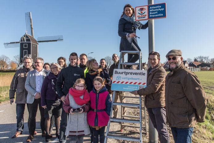 Burgemeester José van Egmond monteert onder het toeziend oog van bewoners het bord dat er op wijst dat in Waarde buurtpreventie geldt.