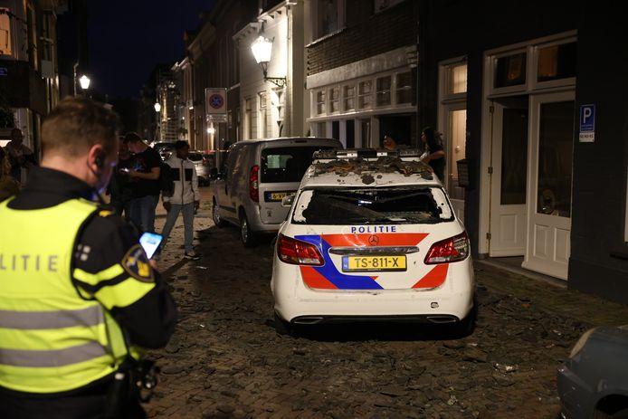 Twee auto's, waaronder deze politiewagen, werden in Kampen vernield door tientallen dakpannen die naar beneden waren gegooid
