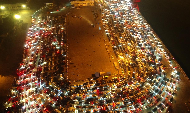 Auto's voor een veerpont in de Chinese stad Haikou. De door de coronacrisis getroffen autoverkoop in China veert verrassend snel terug. Beeld ANP