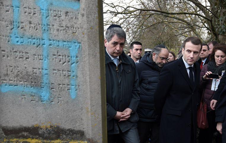 President Emmanuel Macron (r.) wandelde dinsdag tijdens een demonstratie tegen antisemtisme langs een met swastika's beklad graf. Beeld REUTERS