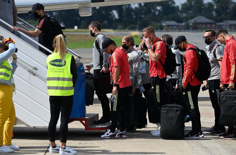 De Rode Duivels stappen het vliegtuig op. Beeld Photo News
