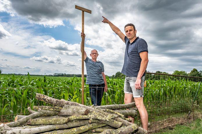 Ad Thomassen (l) en Jeroen Bertens maken bezwaar tegen een zonnepark aan de Oirschotsedijk in Haghorst. Jeroen Bertens wijst op de hoogte van de plaatsen wal rond de zonneweide.