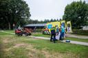 De agenten en het ambulancepersoneel bereiden zich voor om het slachtoffer in de ziekenwagen te tillen.