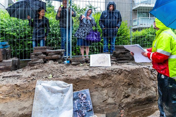 Projectleider Arjan den Braven in de sleuf waar de archeologische opgravingen in Zuilen plaatsvinden. Buurtbewoners kijken in de stromende regen geïnteresseerd toe.