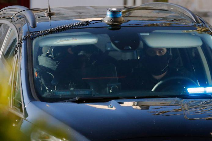 Des policiers de la brigade française escortent dans une voiture de police le chirurgien français retraité Joël Le Scouarnec à son arrivée pour le jour d'ouverture de son procès au tribunal de Saintes, dans l'ouest de la France, le vendredi 13 mars 2020.