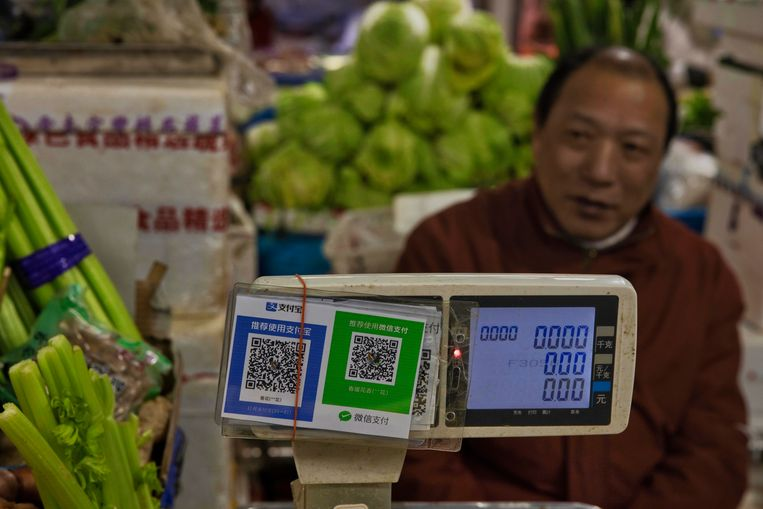 Een groenteverkoper in Shanghai wacht op klanten. hij zit achter de QR-codes van Alipay en WeChat . Beeld EPA