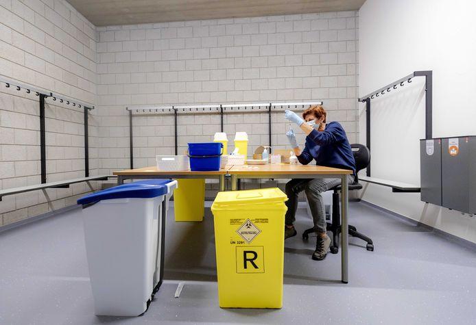 Een medewerker van de GGD maakt spuiten klaar met het AstraZeneca vaccin in een vaccinatielocatie.