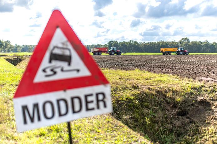 Borden langs de weg waarschuwen voor modder. Tijdens regen kunnen wegen hierdoor spiegelglad worden.
