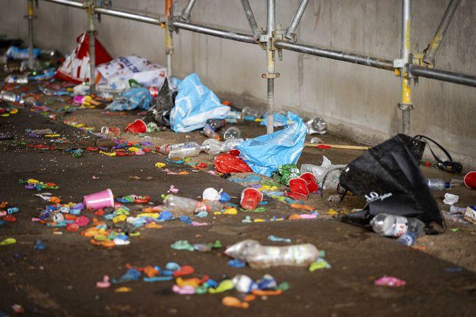Achtergelaten afval onder een viaduct in aanbouw langs een spoorlijn, waar een groot illegaal feest van jongeren door de politie werd beëindigd