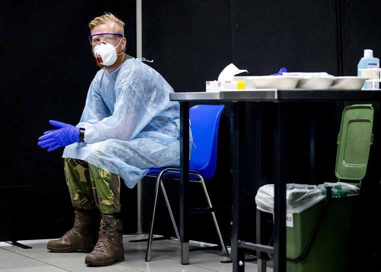 Een militair zit klaar om reizigers uit risicogebieden te testen op corona in de teststraat op Schiphol. Beeld ANP