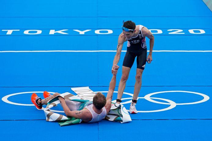 Alex Yee van Groot-Brittannië helpt na de triatlon de Noorse winnaar Kristian Blummenfelt overeind.