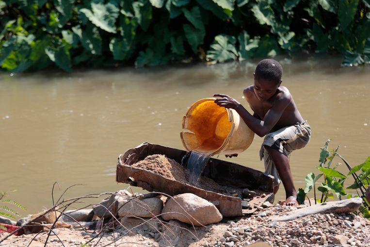 Een Zimbabwaans kind zeeft zand op zoek naar goud. Beeld van november vorig jaar. Beeld EPA