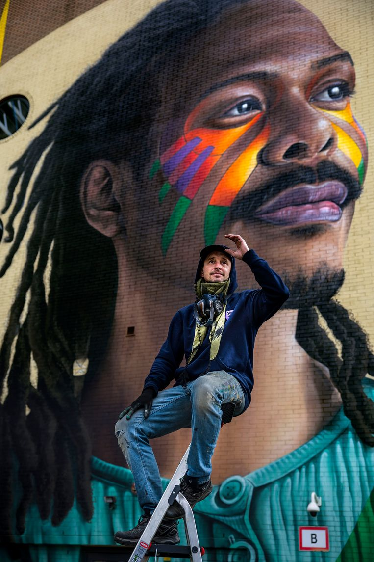 Kunstenaar Tymon de Laat voor zijn muurschildering van Jeangu Macrooy. Beeld Arie Kievit