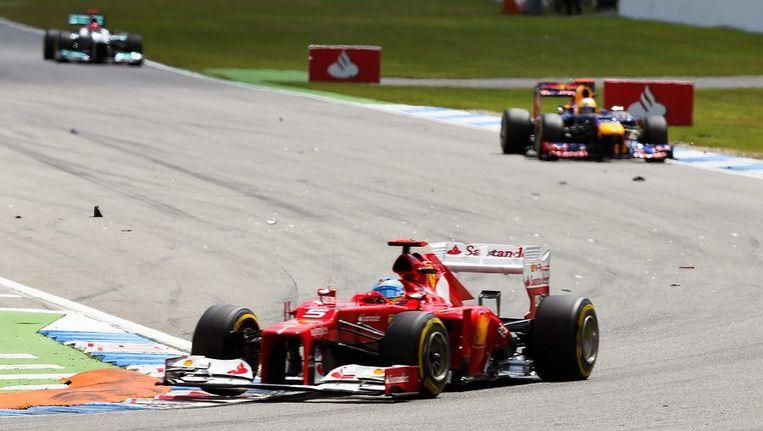Fernando Alonso leidt in zijn Ferrari op Hockenheim, met in zijn kielzog Sebastian Vettel van Red Bull. Beeld epa