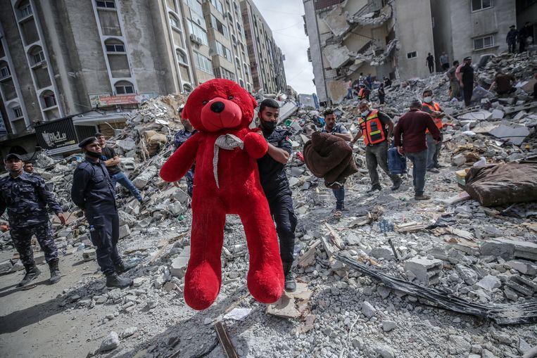 Een reddingswerker houdt een teddybeer omhoog, die in het puin van de ingestorte huizen werd gevonden. Beeld EPA