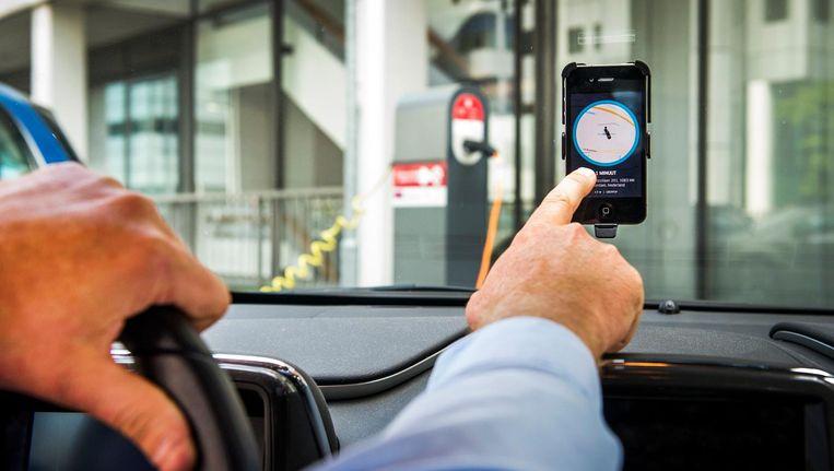 Een chauffeur van Uber accepteert een aanvraag voor een rit van een klant. Beeld anp