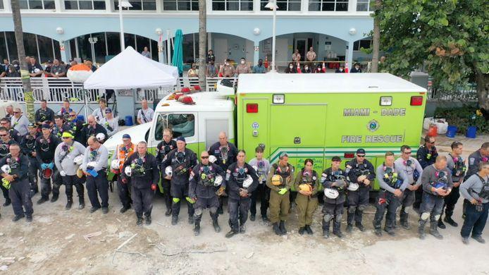 Reddingswerkers houden een moment stilte voor de slachtoffers.