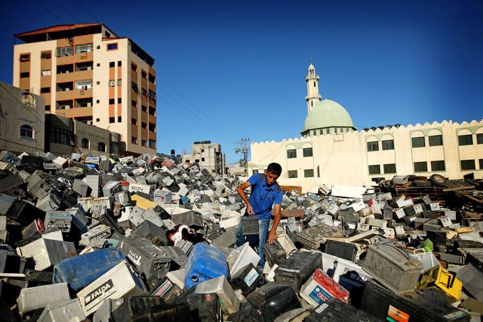 Zou deze nog werken? Een Palestijnse jongen is op zoek naar een nog werkend exemplaar op een enorme hoop afgedankte accu's in Gaza-Stad. Foto: Mohammed Abed