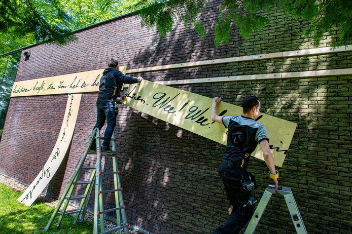 Werklui brengen op het Peerke Donders Paviljoen houten platen aan met een lang citaat uit een brief van de missionaris.