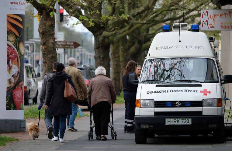 Inwoners van Hannover lopen langs een busje van het Duitse Rode Kruis. In de stad moeten vandaag 50.000 inwoners hun huis tijdelijk verlaten omdat er oude vliegtuigbommen uit de Tweede Wereldoorlog moeten worden geruimd. Beeld AP