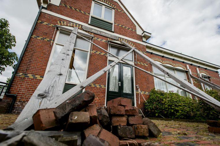 Het dorpshuis in het dorpje Leermens staat gestut door de aardbevingen als gevolg van de gasboringen. Beeld anp