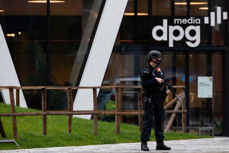 Een gewapende agent bewaakt het gebouw van DPG Media in Antwerpen.  Beeld BELGA