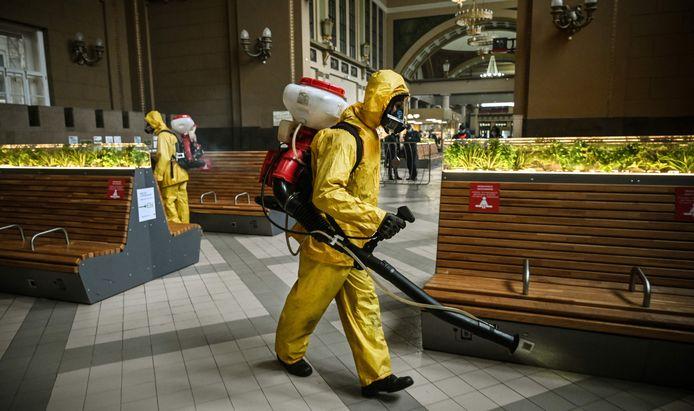 Medewerkers van het Russische ministerie van Noodsituaties desinfecteren een treinstation in Moskou.