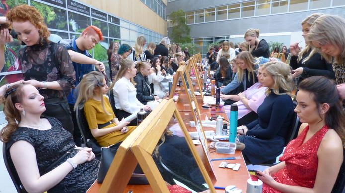 De scholieren van de kappersopleiding druk in de weer met de kapsels