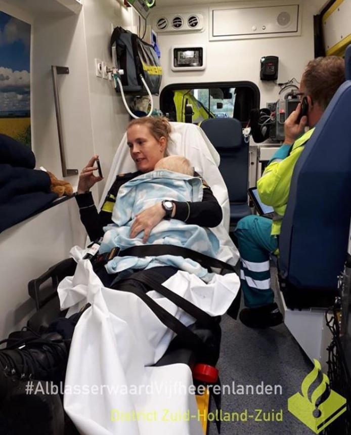 De agente nam de ontroostbare baby op schoot in de ambulance.