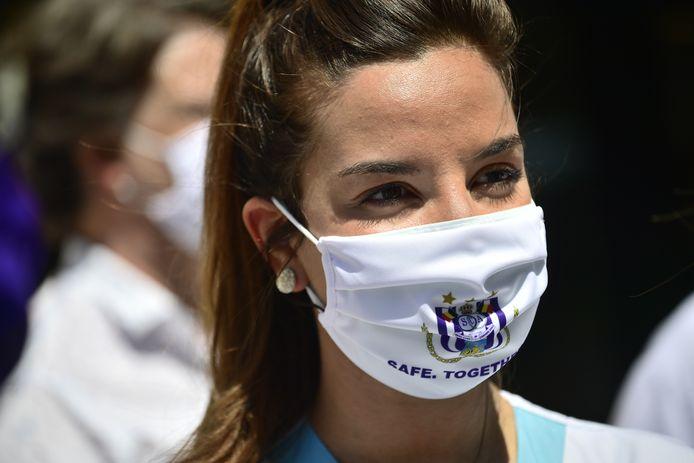 Een vrouw draagt een mondkapje van de Brusselse voetbalclub Anderlecht, tijdens een inzamelingsactie voor ziekenhuizen. De club verkocht de kapjes voor het goede doel.