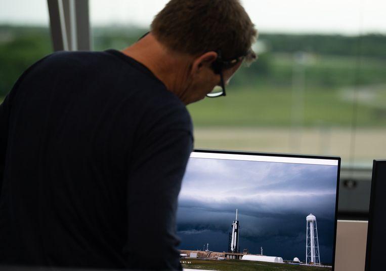 Hans Koenigsmann van SpaceX kijkt woensdagmiddag naar de samenpakkende bewolking boven het lanceerplatform. Ook zaterdag is er een grote kans dat het weer een lancering onmogelijk zal maken. Beeld (NASA/Joel Kowsky)