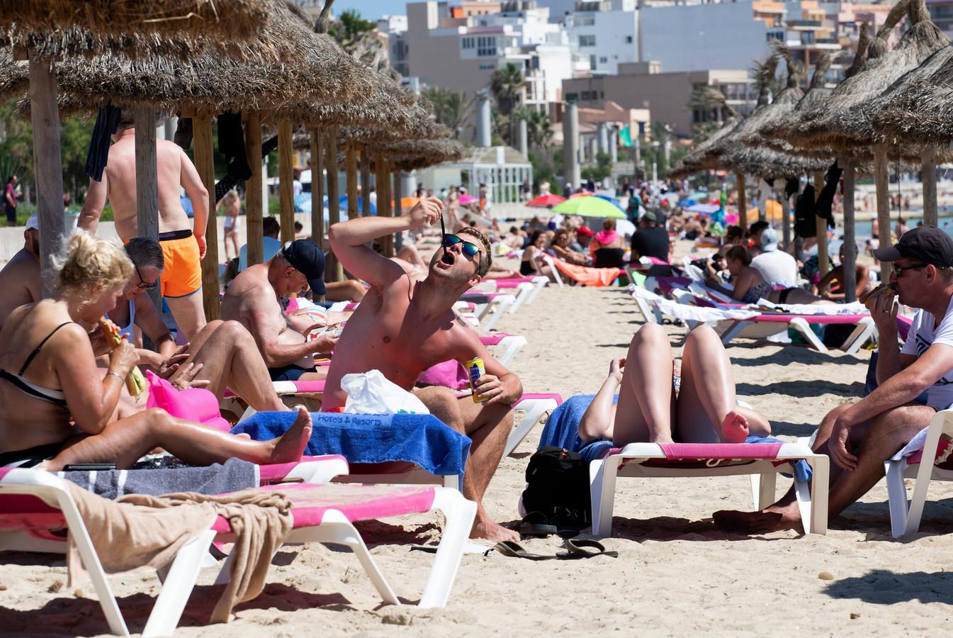 Toeristen genieten van de zon op het strand van Mallorca.