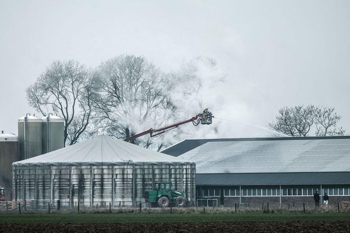 De brandweer blust de stal vanuit een hoogwerker.