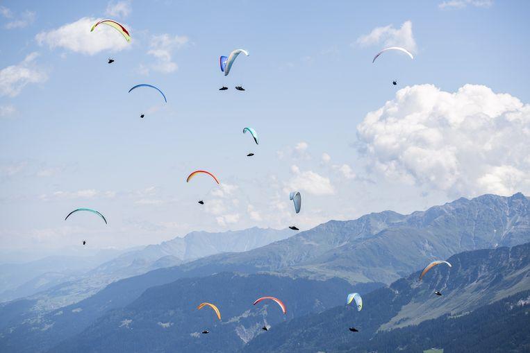 Ook paragliden wordt beoefend in wedstrijdverband. De finalisten die hier door de lucht boven Disentis in Zwitserland zweven, strijden om de wereldbeker. Ze moeten een route langs vaste GPS-punten zo snel mogelijk afleggen.  Beeld EPA