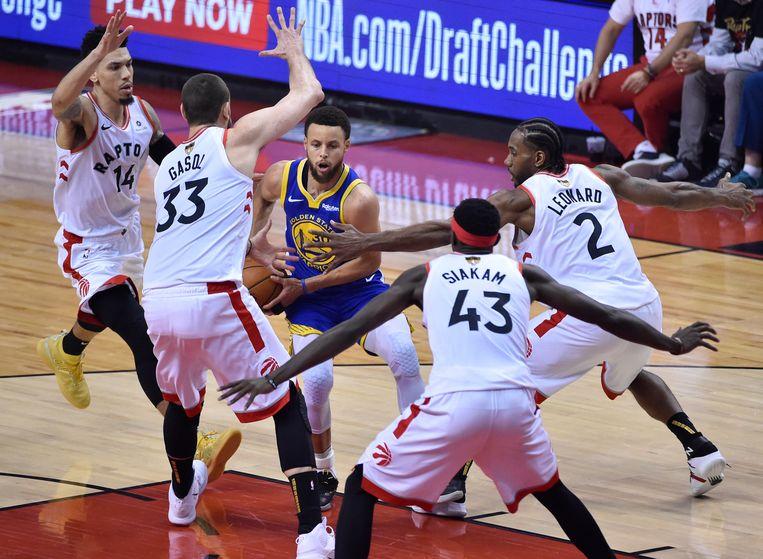 Curry (in blauw shirt) omringd door spelers van de Raptors. Beeld EPA