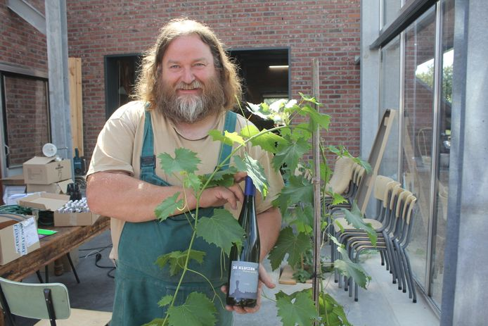 Wijnbouwer Herman Troch met een van de wijnen die hij maakte van de oogst van 2014 in de nieuwe serre. In de betonvloer zijn gaten gelaten waarin druivelaars zijn geplant.