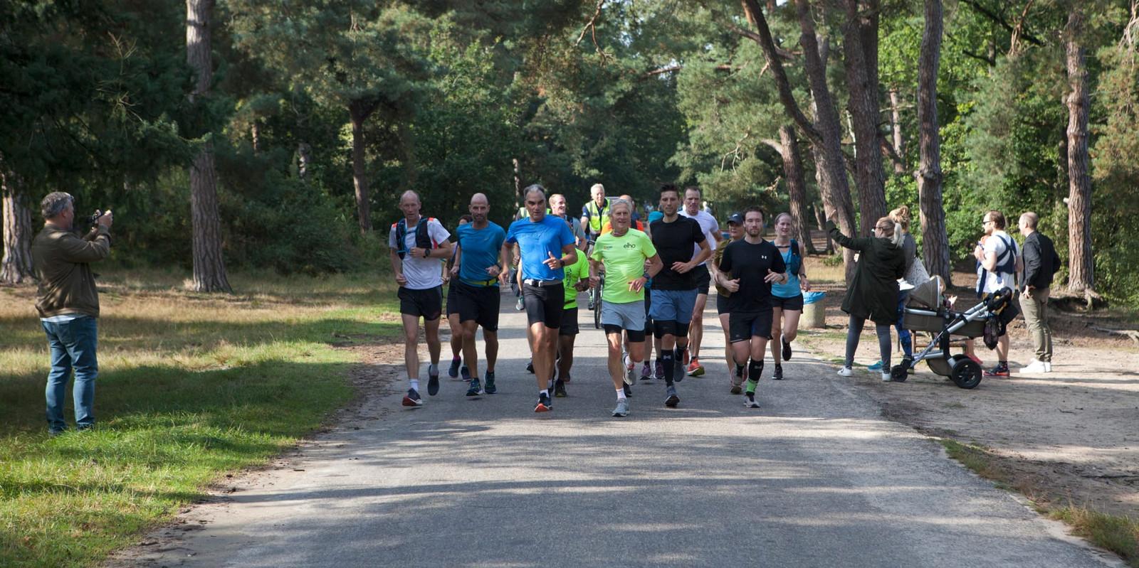 Wim Akkermans (in het gele shirt) werd zondag tijdens de tocht van uiteindelijk zo'n 80 kilometer de hele tijd begeleid door andere lopers.